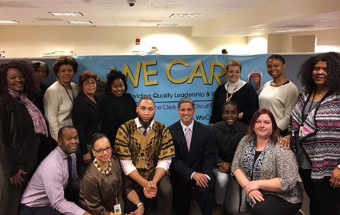 Clerk of Court Sydney Harrison and staff in front of We Care poster